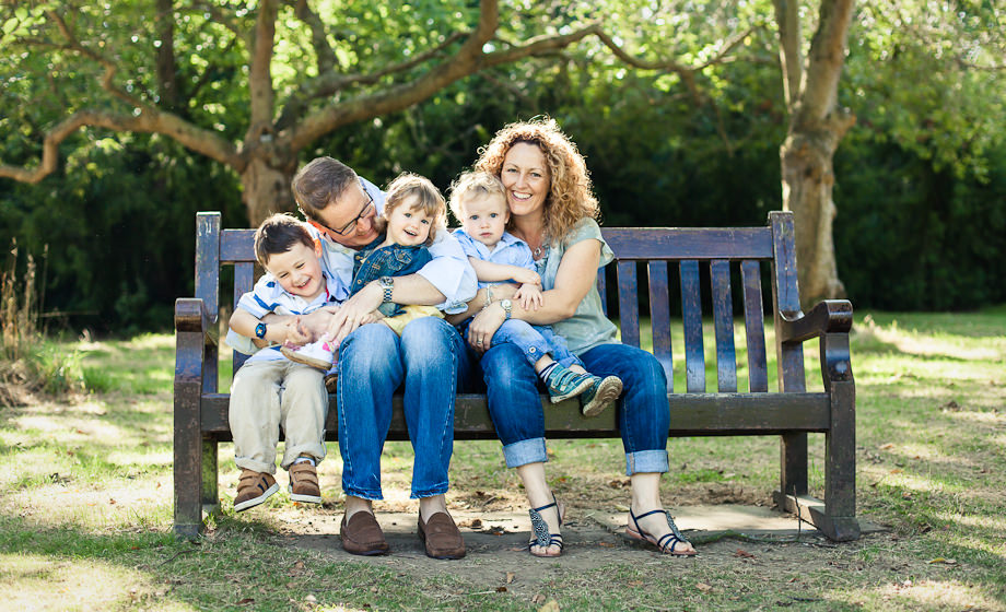 family laughing on bench